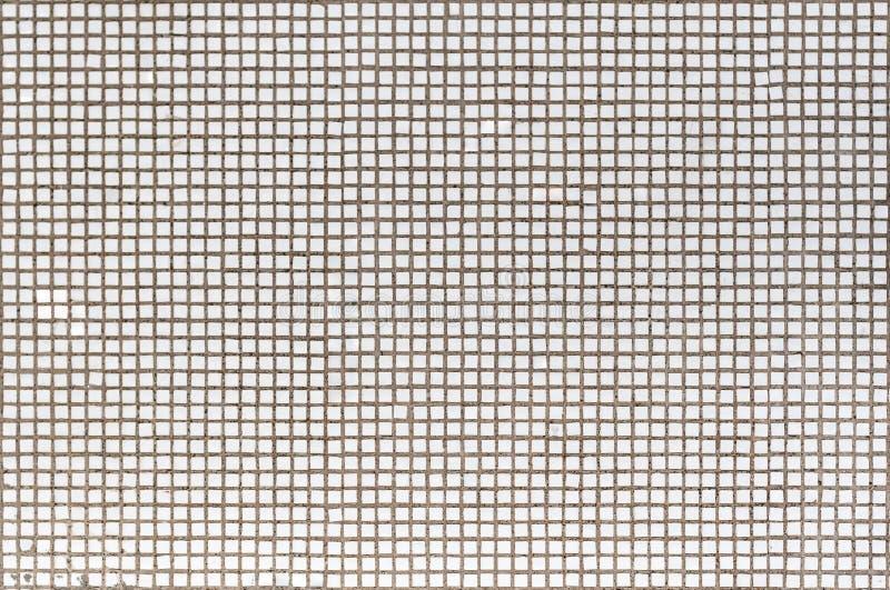La pared vieja de la casa se adorna con un pequeño mosaico blanco fotografía de archivo libre de regalías