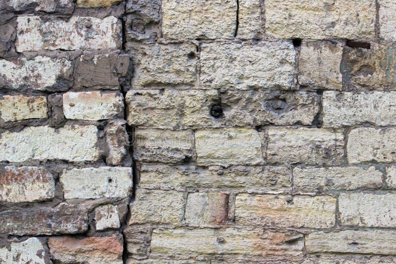 La pared vieja de curvas beige de ladrillos con una toba volcánica calcárea de las piedras históricas grandes de la grieta Gatchi imágenes de archivo libres de regalías