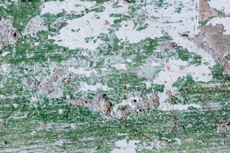 La pared vieja del cemento con verde comenzó a pelar apagado imagenes de archivo