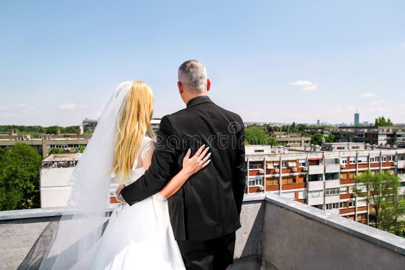 La pareja casada hermosa que se coloca en el tejado y mira la ciudad urbana imagenes de archivo