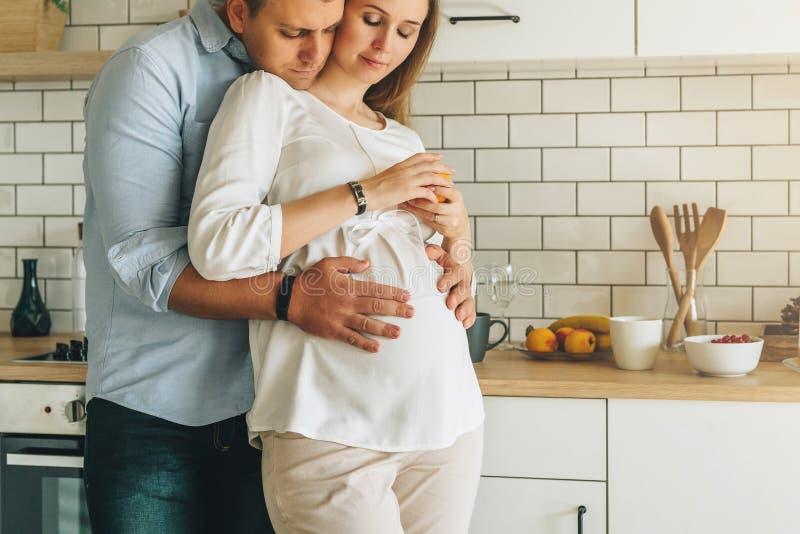 La pareja casada los jóvenes abraza la tabla cercana derecha en cocina El marido abraza a su esposa embarazada Forma de vida, gen imagen de archivo libre de regalías
