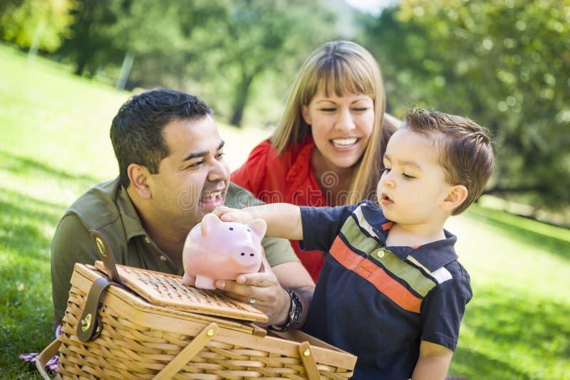 La pareja de la raza mixta da a su hijo una hucha en el parque
