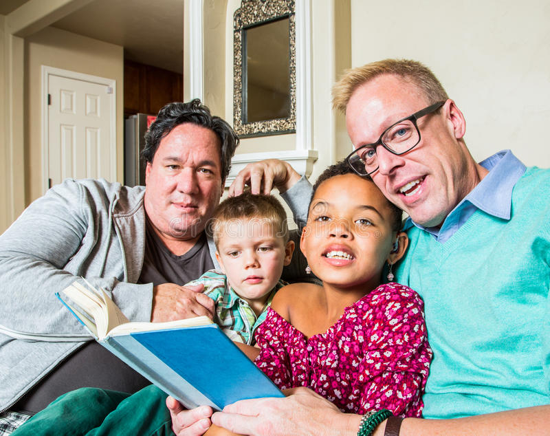 La pareja gay lee a los niños imagen de archivo