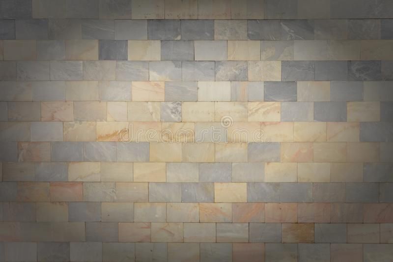 La parete è fatta delle mattonelle grige ed arancio di marmo Bella struttura di pietra Fondo vuoto con la scenetta fotografia stock libera da diritti