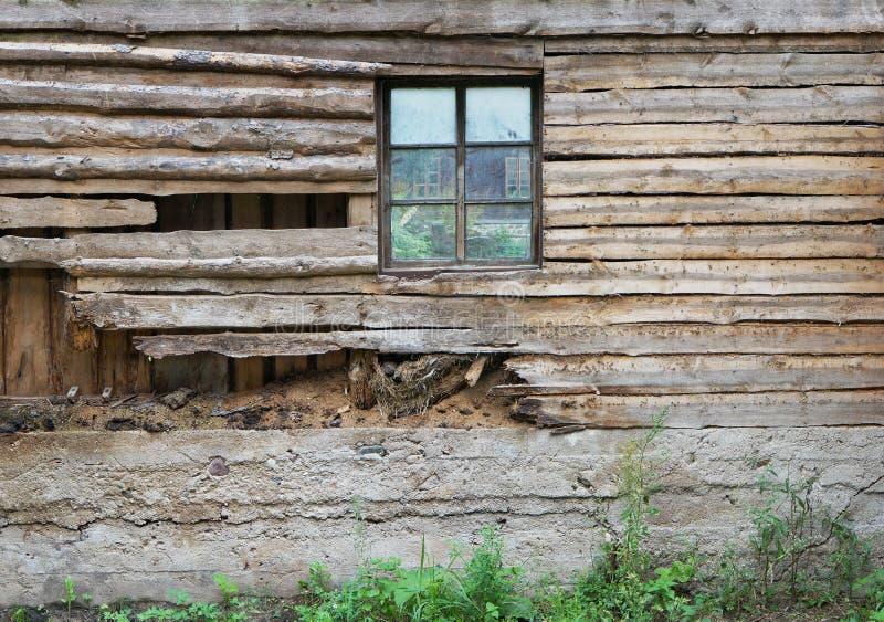 La parete di legno marcia di un granaio del villaggio con una finestra fotografia stock libera da diritti