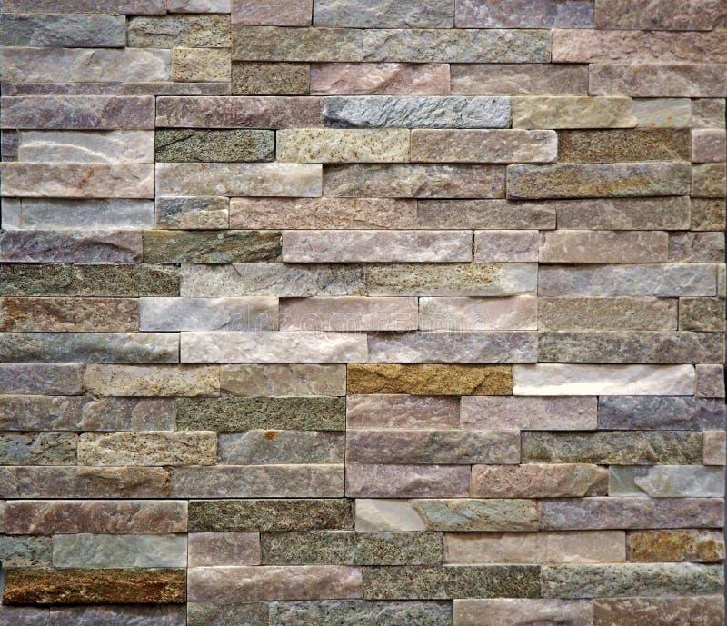 La parete di pietra del rivestimento fatta del barrato di ha impilato le lastre multicolori delle rocce naturali immagini stock libere da diritti