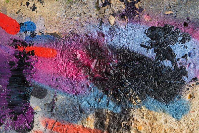 La parete di pietra ha macchiato le toppe variopinte degli aerosol luminosi di colori Cultura urbana iconica moderna della gioven fotografie stock
