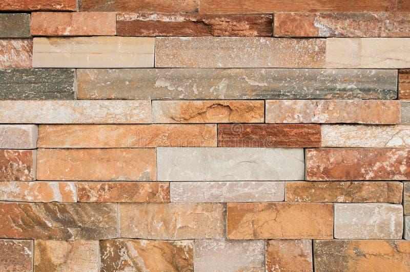La parete di pietra marrone di lerciume piastrella la struttura Pietra marrone della parete e arancio naturale sporca, polvere co fotografie stock libere da diritti