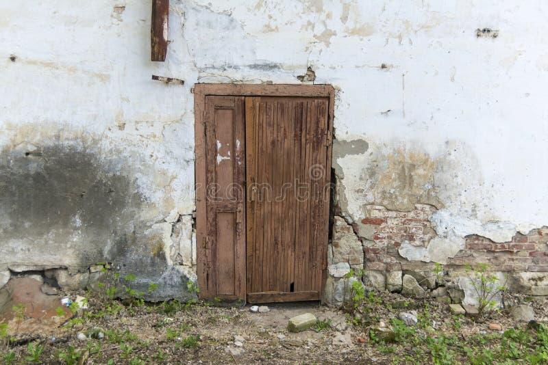 La parete di vecchia casa con una porta Cad da da gesso, muro di mattoni fotografia stock libera da diritti
