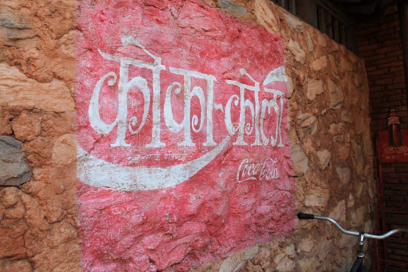 La parete dipinta di Coca-Cola firma dentro la lingua straniera fotografia stock