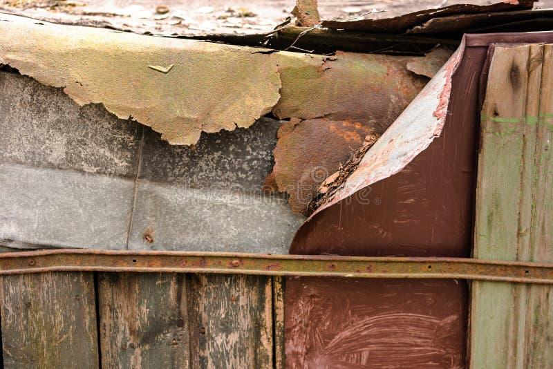 La parete distrutta del villaggio è di metallo arrugginito e dei bordi stagionati immagine stock libera da diritti