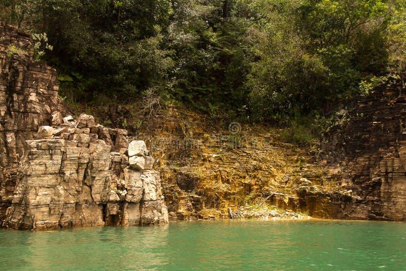 La parete dorata riflette il suo colore nell'acqua fotografia stock