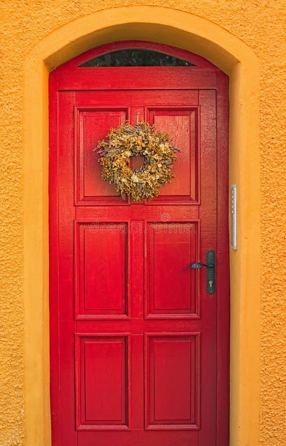 La parete giallo arancione luminosa di vecchia casa rustica con la porta di legno rossa decorata con una corona del campo fiorisc fotografia stock libera da diritti
