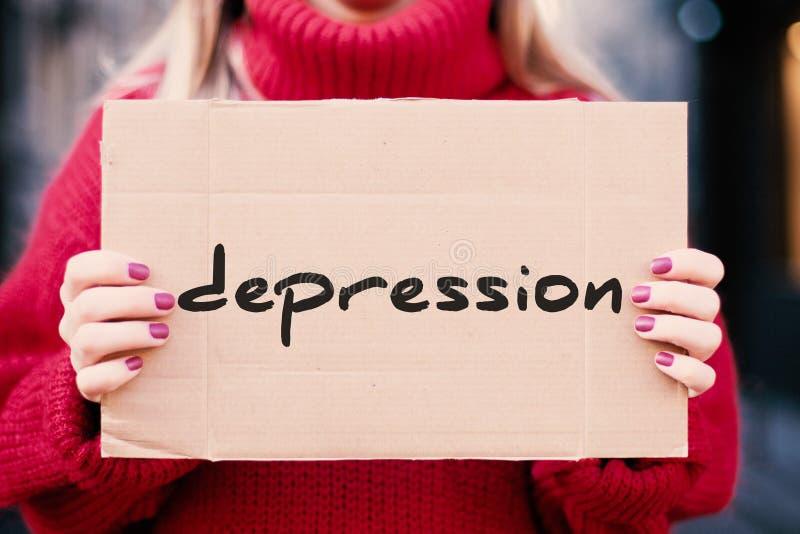 """La parola """"depressione """"nelle mani di una ragazza sulla via, scritte su un piatto del cartone fotografia stock"""