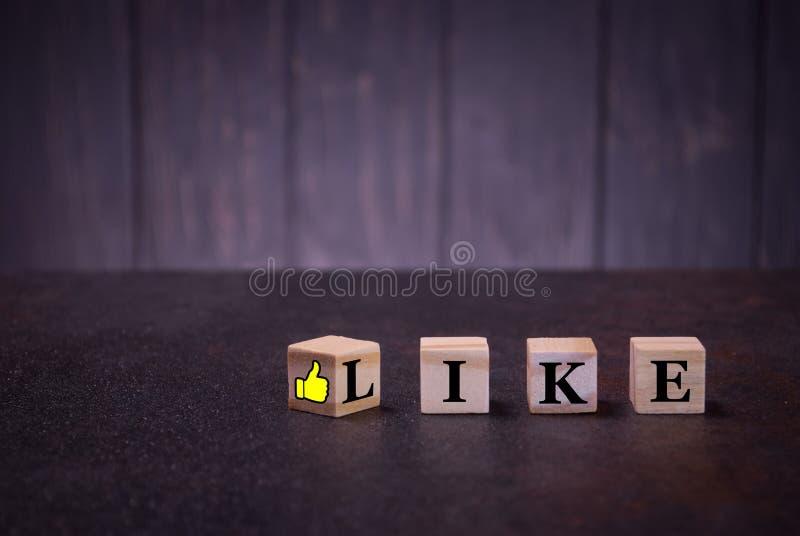 La parola come ed il pollice di sospiro su sui cubi di legno, su un fondo scuro, segni di legno leggeri dei cubi fotografie stock