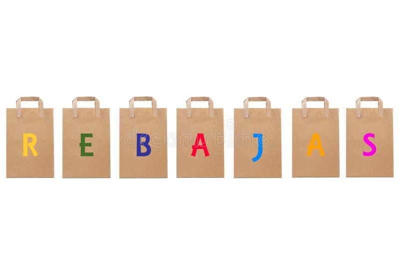La parola di vendita di Rebajas scrive in sacchi di carta differenti immagini stock libere da diritti