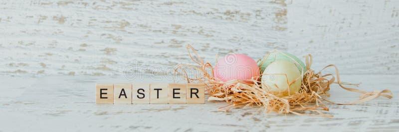 La parola Pasqua è dei segni di legno leggeri e delle uova dipinte in una n immagini stock libere da diritti