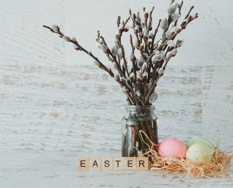 La parola Pasqua dai piatti di legno leggeri, ramoscelli del salice con la guarnizione fotografia stock libera da diritti