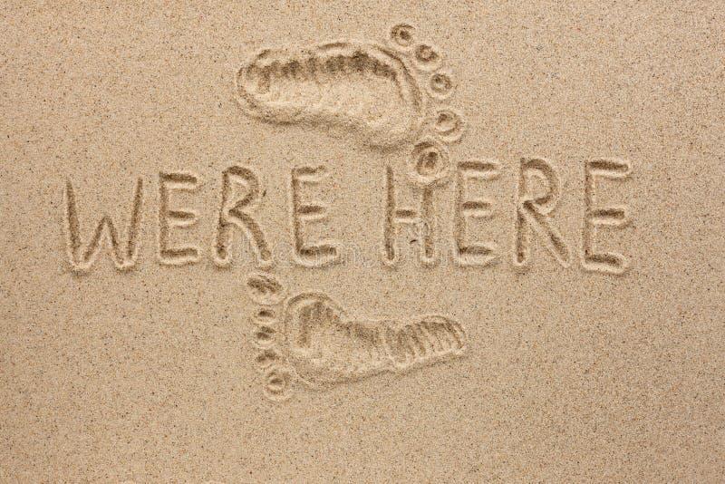 La parola QUI è stata scritta sulla sabbia fotografia stock