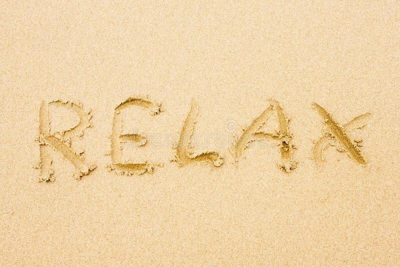 La parola si distende scritto sulla sabbia fotografia stock libera da diritti