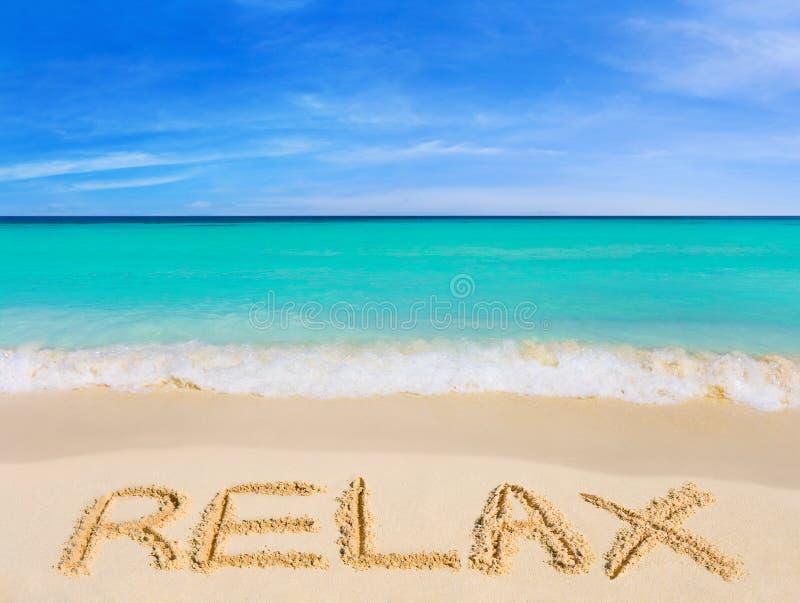 La parola si distende sulla spiaggia immagini stock