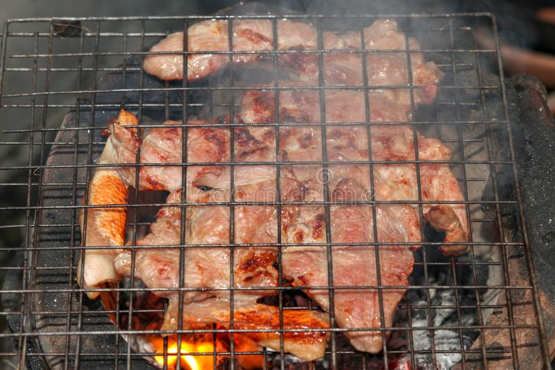 la parrilla Carbón de leña-hervida del cuello del cerdo en estufa vieja tiene humo en Tailandia fotografía de archivo