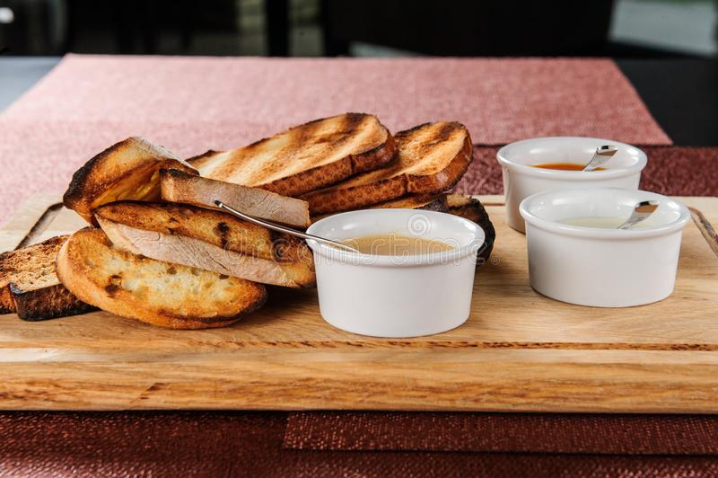 La parte de la tostada asada adentro empanada con queso y sésamo se deslizó en una salsa en un tablero de madera foto de archivo