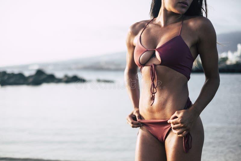 La parte del cuerpo morena del primer en bikini rojo toma un sunbath y una actitud como un modelo que muestra el pecho y el vient fotografía de archivo