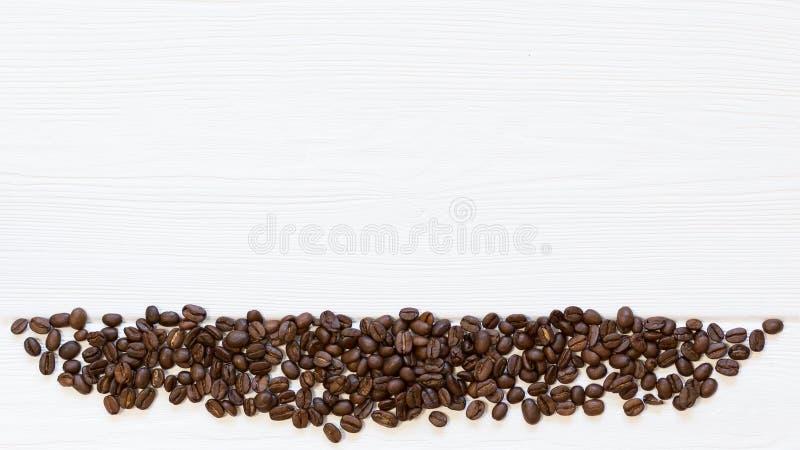 La parte del telaio ha arrostito i chicchi di caffè giù su fondo di legno bianco, vista superiore Spazio della copia, posto liber immagini stock