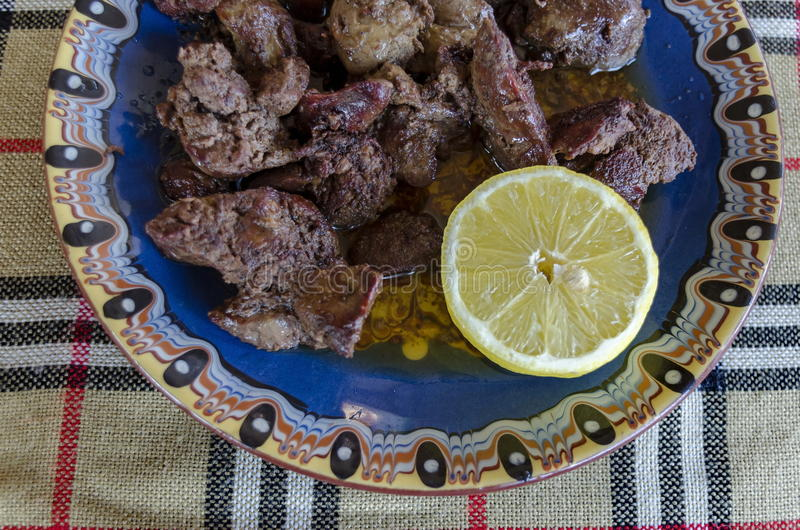La parte di fegato di pollo ha arrostito con burro ed il limone nel piatto dell'argilla immagine stock libera da diritti