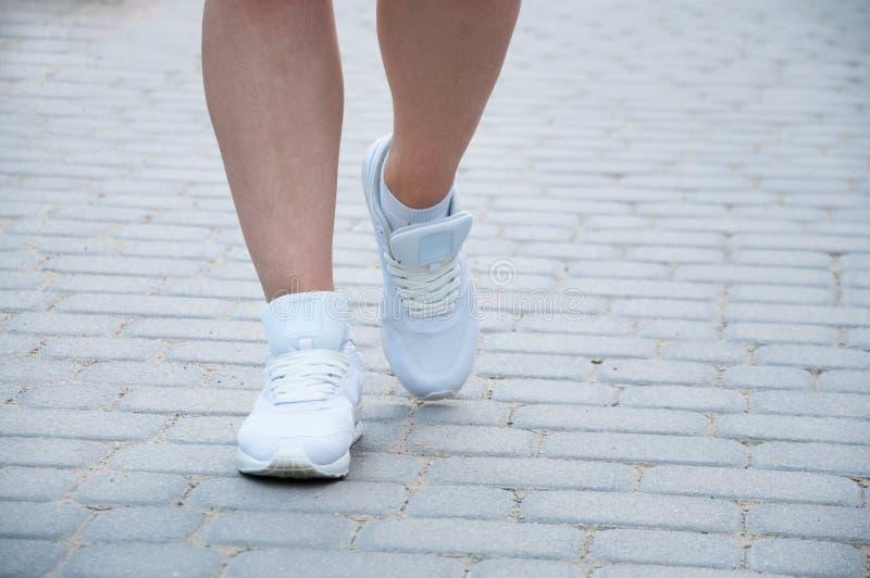 La parte inferiore delle gambe di una donna in scarpe da tennis bianche Va lungo i vicoli di estate fotografie stock libere da diritti
