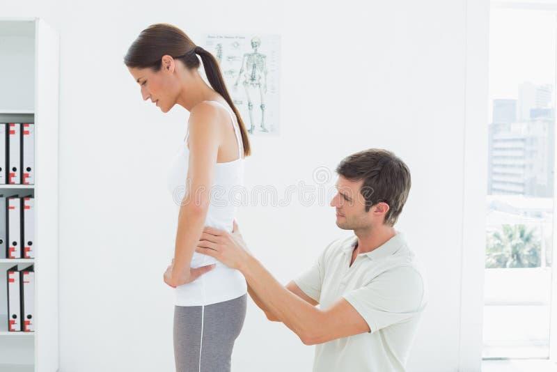 La parte posterior de la mujer de examen del fisioterapeuta en oficina médica imagen de archivo libre de regalías
