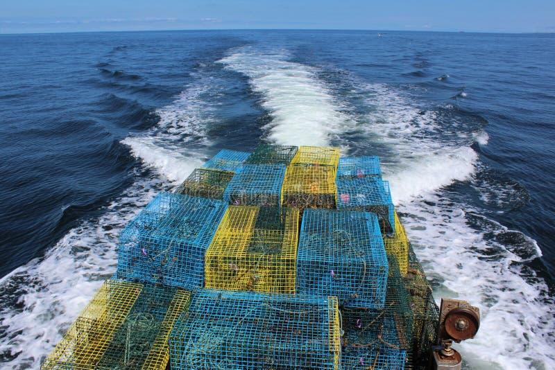 La parte posterior de un barco de la langosta por completo de las trampas que vuelven en el día pasado de la temporada de pesca imagen de archivo libre de regalías