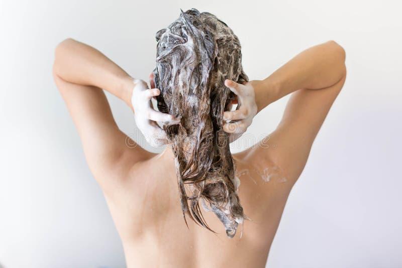 La parte posterior de una mujer que se lava el pelo por completo de la birra delante de un fondo blanco fotografía de archivo
