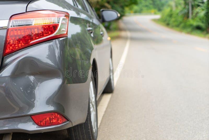 La parte posterior del coche gris consigue dañada de accidente en el camino Abolladura de parachoques del vehículo rota por choqu fotos de archivo libres de regalías