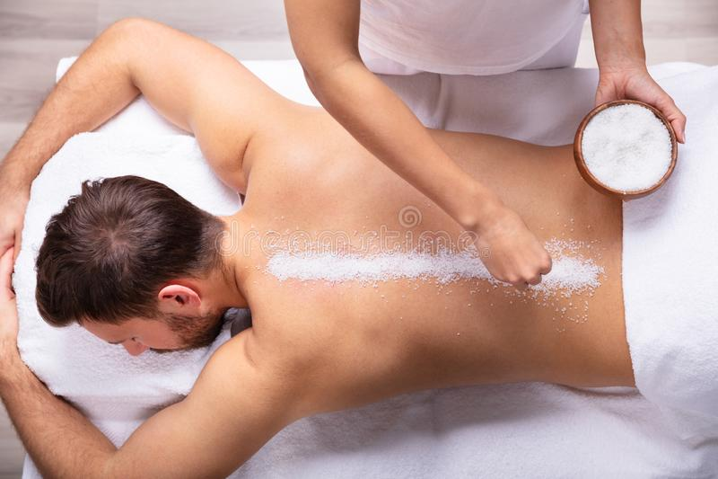 La parte posterior del hombre de Applying Salt On del terapeuta foto de archivo libre de regalías