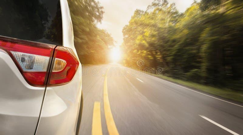 La parte posteriore alta vicina dell'automobile sta correndo sulla strada asfaltata di estate fotografie stock