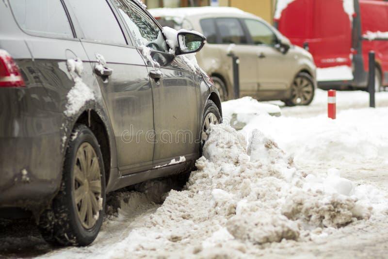 La parte posteriore del dettaglio del primo piano dell'automobile ha parcheggiato in neve profonda nel parcheggio immagini stock