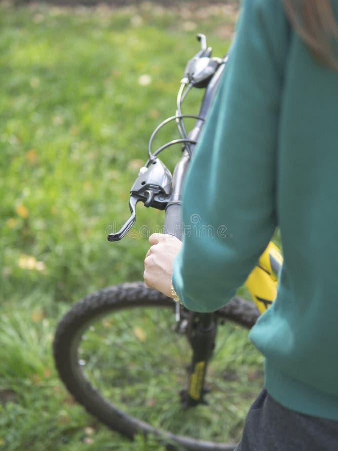 La parte posteriore sexy della giovane donna sexy sulla bicicletta fissa rossa dell'ingranaggio di stile di sport che posa sulla  immagine stock