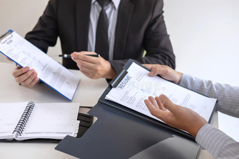 La participation d'employeur ou de recruteur lisant un résumé pendant environ l'entretien son profil du candidat, employeur dans  photo libre de droits