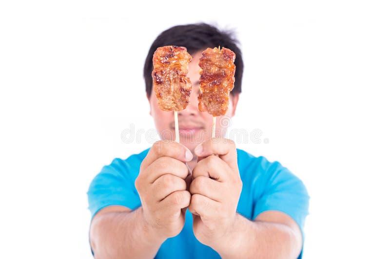 La participation d'homme a grillé le porc dans l'isolat en bambou de bâton sur le blanc photos stock