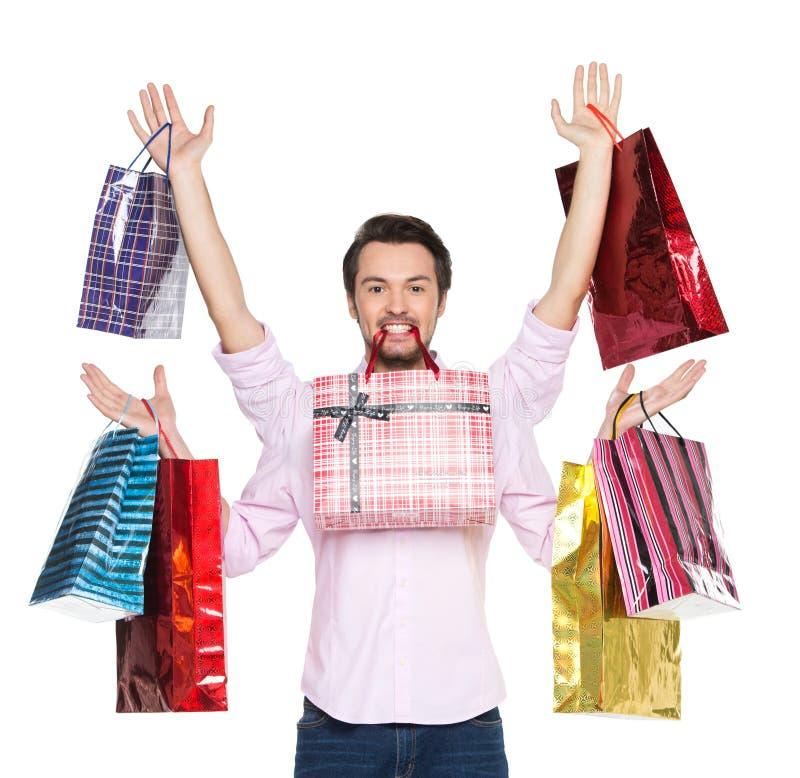 La participation d'homme présente dans des sacs en papier de cadeau, d'isolement sur le blanc photo stock