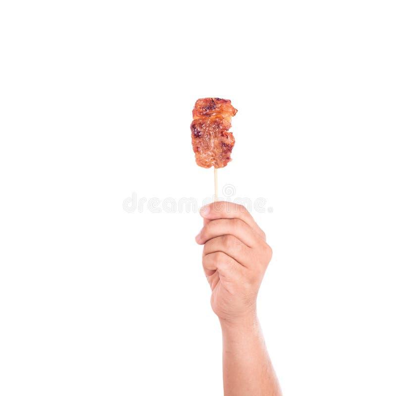 La participation de main a grillé le porc dans l'isolat en bambou de bâton sur le blanc images libres de droits