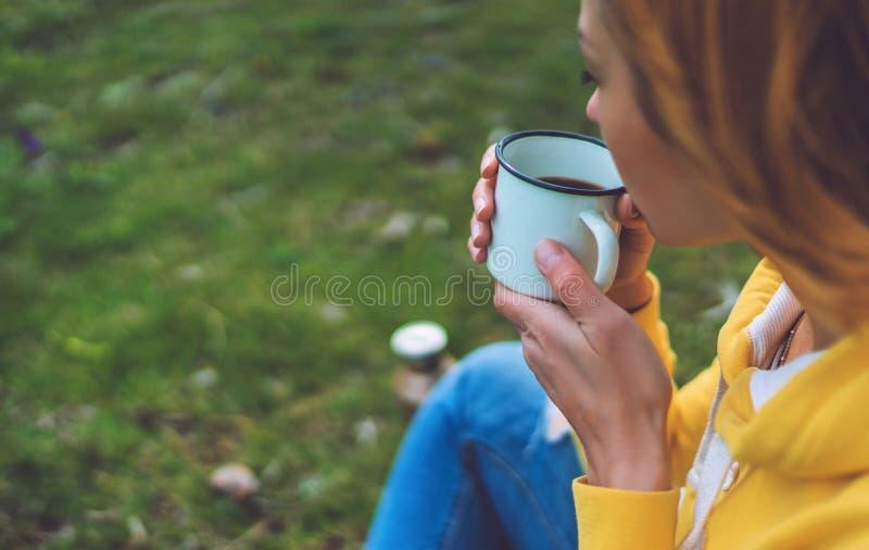 La participation heureuse de fille dans la tasse de mains de th? chaud sur l'herbe verte en parc naturel d'ext?rieur, belle hippi photographie stock
