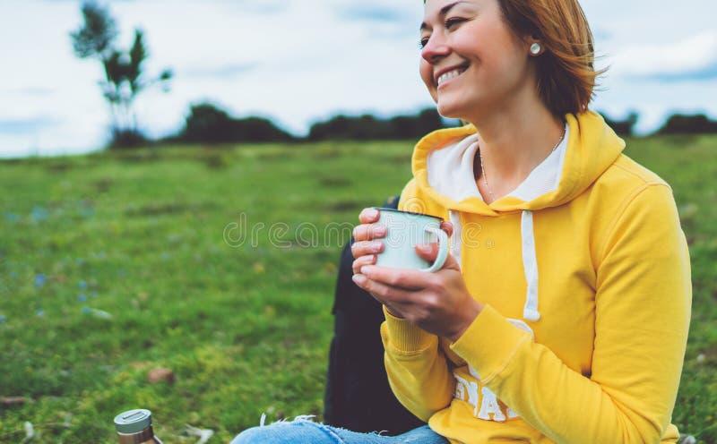 La participation heureuse de fille de sourire dans la tasse de mains de thé chaud sur l'herbe verte en parc naturel d'extérieur,  image stock