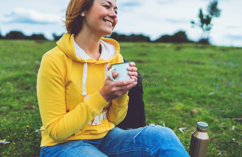 La participation heureuse de fille de sourire dans la tasse de mains de th? chaud sur l'herbe verte en parc naturel d'ext?rieur,  photos stock