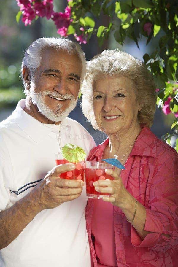 La participation supérieure heureuse de couples boit dehors photographie stock