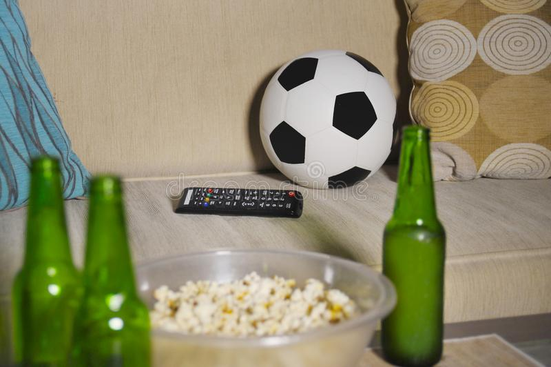 La partie de football de observation conceptuelle au sofa à la télévision avec des bouteilles à bière et le maïs éclaté roulent d image stock