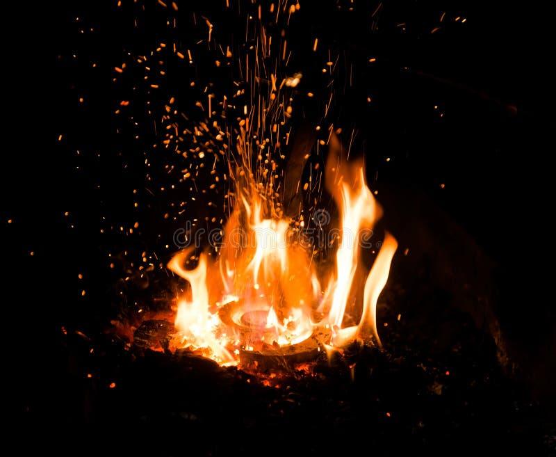 La partie en acier est passionnée dans le feu avant la forge photographie stock libre de droits