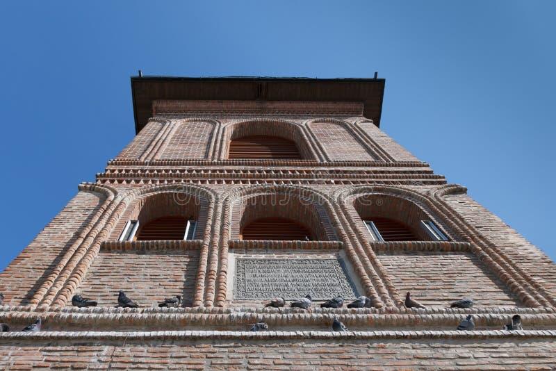 La partie supérieure de la vieille façade de brique de la tour de cloche avec les pigeons se reposants Colline métropolitaine, Bu image libre de droits